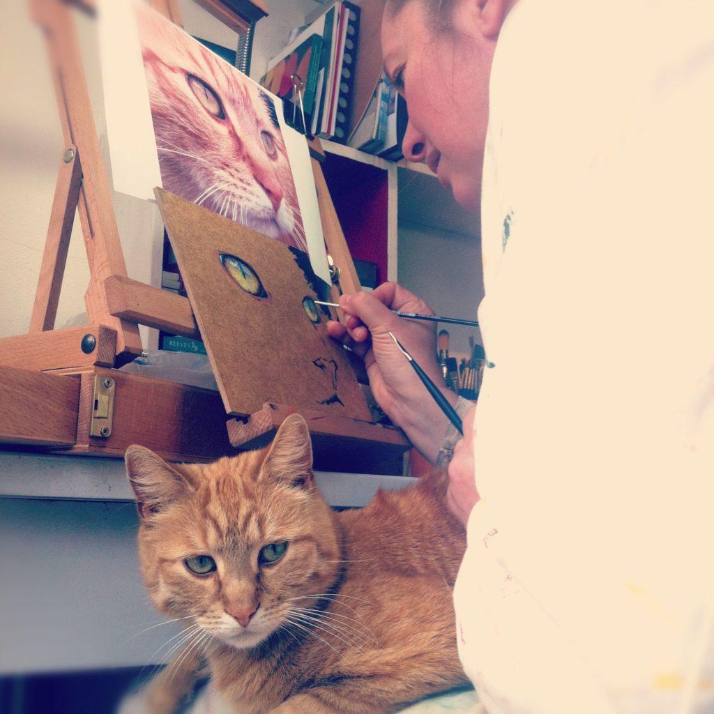 Sasja Bork schildert haar kat met het model op schoot