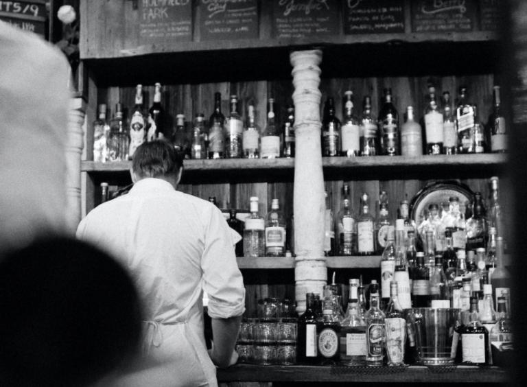 zwart wit foto van kelner voor bar